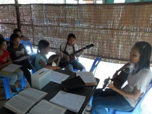 Darlin, Srey Nich and Sokha playing the guitar and singing during Sunday worship