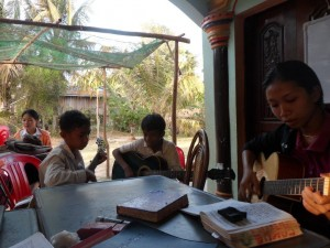 Pisey, Bolong, and Veasna playing the guitar before the to start an English Outreach class